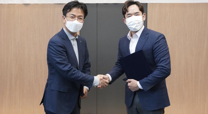 Yoon Dae-gyu (of Hyundai Robotics) and Yoon Seong-ho (of MakinaRocks) shaking on the company partnership