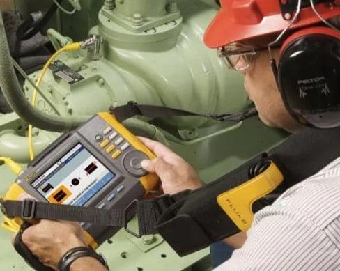 A technician uses the Fluke 810 Vibration Tester.